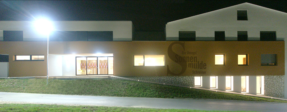 View towards the illuminated winery at night