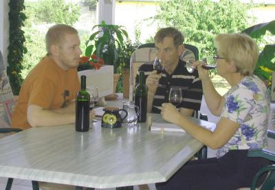 Hans, Renate and Andreas sit at a terrace table with wine bottles and glasses on top