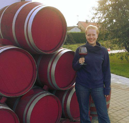 Kathrin is standing with a glass of grape juice next to a stack of red painted barrique barrels which serve as decoration in the garden.