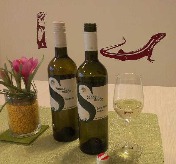 On a table there are two wine bottles, one of them open. Next to it a slightly filled glass and a vase with decoration. In the background are graphics with a ground squirrel and a lizard on the wall.
