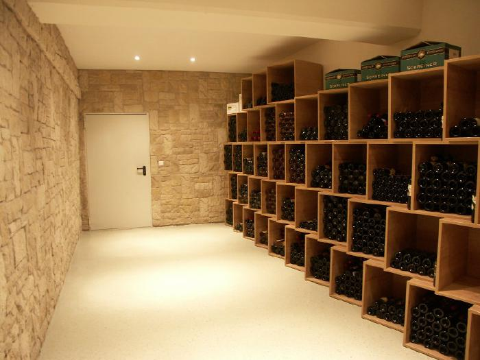 An elongated room with stone walls on the left and at the head end where there is also a door. The right wall is taken up by shelves with compartments for wine bottles.