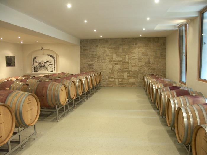 Cellar with central corridor and stone wall at its end. Barrique barrels lined up on metal racks to the left and right of the aisle.