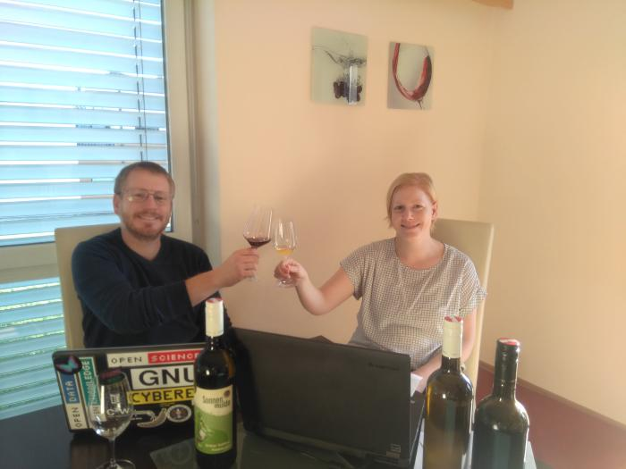 Kathrin and Andreas are sitting at a table with two laptops on it. They toast each other with two wine glasses. There are a few wine bottles on the table.