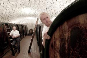 Andreas and Hans between big wooden casks. Hans has one foot on a ladder, Andreas looks out from behind one of the casks.