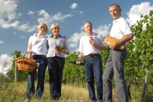 The Schreiner Family with bread, wine and a picnic basket between rows of grapevines