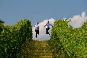 Kathrin and Andreas run downhill between rows of grapevines and jump into the air with stretched-out feet.